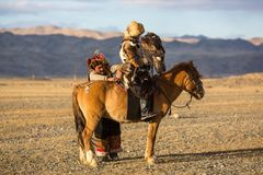 Eagle Hunter teaches her young daughter hunting. SAGSAY, MONGOLIA - SEP 28, 2017: Eagle Hunter teaches her young daughter hunting with birds of prey to the hare Stock Images