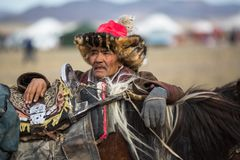 Eagle Hunter at traditional clothing during annual national competition with birds of prey `Berkutchi` of West Mongolia. royalty free stock photography