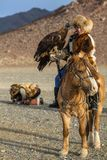 Eagle Hunter, young daughter hunting with birds of prey to the hare in desert mountain of Western Mongolia. SAGSAY, MONGOLIA - SEP 28, 2017: Eagle Hunter, young Royalty Free Stock Photography