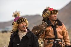 Eagle Hunters an der traditionellen Kleidung, mit einem Steinadler auf seinem Arm während des jährlichen nationalen Wettbewerbs m Lizenzfreies Stockfoto