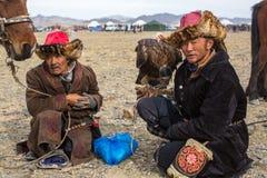 Eagle Hunters an der traditionellen Kleidung, mit einem Steinadler auf seinem Arm während des jährlichen nationalen Wettbewerbs m Lizenzfreie Stockfotos