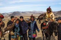 Eagle Hunters an der traditionellen Kleidung, mit einem Steinadler auf seinem Arm während des jährlichen nationalen Wettbewerbs m Stockbild