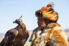 Eagle Hunters an der traditionellen Kleidung, mit einem Steinadler auf seinem Arm während des jährlichen nationalen Wettbewerbs m Lizenzfreie Stockbilder