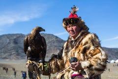 Eagle Hunters an der traditionellen Kleidung, mit einem Steinadler auf seinem Arm während des jährlichen nationalen Wettbewerbs m Lizenzfreies Stockbild