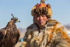 Eagle Hunters dorato kazako ad abbigliamento tradizionale, durante la concorrenza nazionale annuale con il ` di Berkutchi del ` d Fotografie Stock Libere da Diritti