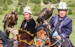 Eagle Hunters hold their eagles, ready for action. Issyk Kul, Kyrgyzstan - May 29, 2017: Eagle Hunters hold their eagles, ready for action Royalty Free Stock Photography