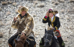 Eagle huntress and her dad. Bayan Ulgii, Mongolia, October 4th, 2015: Eagle huntress with her dad riding a horse Stock Photos