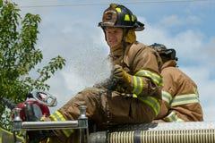 EAGLE/IDAHO - 6月9日:在他的救火车顶部的消防员,在老鹰后的老鹰乐趣天期间他打开了他的firehose,爱达荷 库存图片