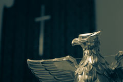 Eagle Lectern with Blurred Cross in the Background Royalty Free Stock Images