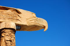 Eagle and Lion Wood Carving Totem Pole. Eagle and lion wood carved totem pole is set against a brillant clear blue sky Stock Image