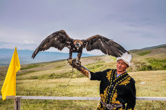 Eagle man in Kyrgyzstan. Karakol, Kyrgyzstan - circa July 2011: Native man dressed in traditional folk costume poses with Golden eagle on his arm at Karakol Royalty Free Stock Images