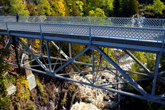 Eagle River Falls. Is observed by a woman standing on the Eagle River Bridge in Upper Peninsula, Michigan.  Autumn colors hillside and gorge Royalty Free Stock Images