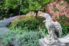 Eagle-Skulptur in einem Garten voll von Blumen Stockfotografie