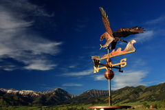 Eagle Weather Vane. A copper eagle weather vane points toward the Montana mountains stock photo