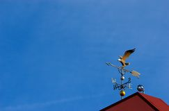 Eagle weather vane. A realistic bald eagle weather vane on top of a red roof, clear blue sky background royalty free stock photos