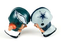 Eagles and Cowboys go helmet to helmet Li`l Teammates on Black Backdrop.  royalty free stock photography