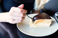 Eaing与匙子的蛋白牛奶酥蛋糕在咖啡馆 免版税图库摄影