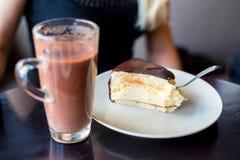 Eaing与匙子的蛋白牛奶酥蛋糕在咖啡馆 库存图片