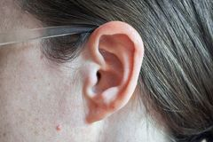 Ear and auricle, part of cheek, hair, skin and glasses. stock image