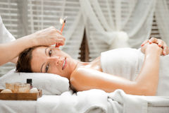 Ear Candling in Spa. Ear candling being carried out on an attractive caucasian woman in a spa Royalty Free Stock Photography