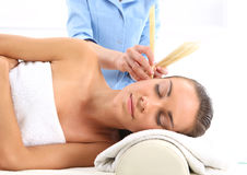 Ear candling. Woman relaxes in the study of natural medicine. ear candling treatment Stock Photo
