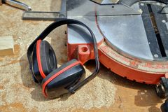 Ear Defenders lying on working table next to a chop saw royalty free stock image