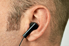 Ear with earphone closeup Stock Images