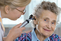 Ear exam. Doctor performing ear exam with otoscope stock photography