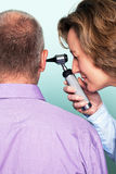Ear examination. Photo of a female doctor examining a patients ear using an otoscope