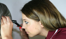 Ear Examination. A pretty nurse examines a patient to check for an ear infection stock photography