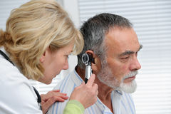 Ear examination. ENT physician looking into patient's ear with an instrument royalty free stock photo
