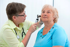 Ear examination. ENT physician looking into patient's ear with an instrument stock photos