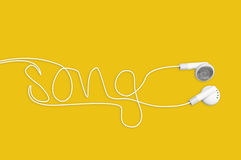 In ear headphones writing song on yellow Royalty Free Stock Photography