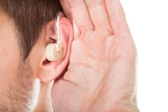 Ear with hearing aid. Close-up Of An Ear With Hearing Aid Royalty Free Stock Images
