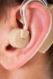 Ear with hearing aid. Close-up Of An Ear With Hearing Aid stock photography