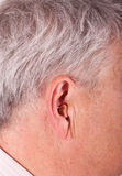 Ear with hearing aid. Close-up of a senior man's ear wearing a CIC (Completely In the Canal) hearing aid stock photography