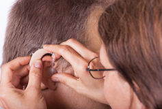 Ear and hearing aid insertin close up Stock Images