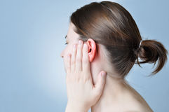 Ear inflammation. Young woman touching her inflamed ear Royalty Free Stock Image