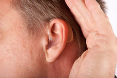 Ear of a man close up with hearing aid. Stock Images