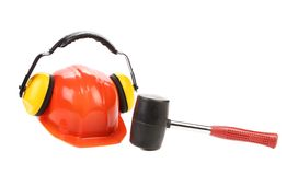 Ear muffs on hard hat and hammer. Royalty Free Stock Image