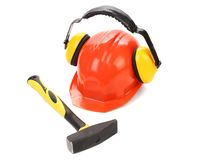 Ear muffs on hard hat and hammer. Stock Photography