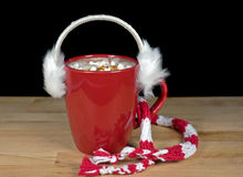 Ear muffs on hot chocolate drink Royalty Free Stock Image