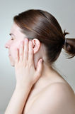 Ear pain. Young woman touching her painful ear Stock Photos