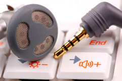 Ear phone. S on white notebook keyboard. s and jack are in focus, background white and blurred Royalty Free Stock Images