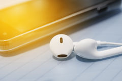 Ear phone into smart phone mobile. On blurred background color filter style Stock Image