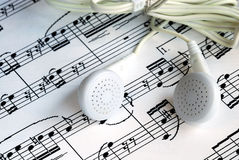 An ear phone on the top of a music sheet Stock Photography