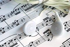 An ear phone on the top of a music sheet. An ear phone is on the top of a music sheet Stock Photography
