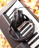 Ear-phones lie on the piano. Royalty Free Stock Photography
