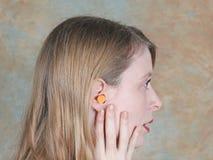 Ear plug inside. Young girl wearing ear plug inside her ear lobe Stock Image