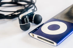 Ear plug with the music player. Ear plug with the blue music player on the white background Royalty Free Stock Photography